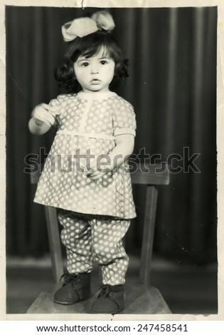 USSR - CIRCA 1980s: Vintage photo show girl with bow standing on a chair - stock photo