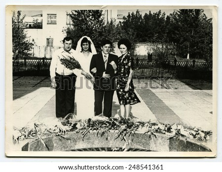 USSR, Petrapavlovsk - CIRCA 1980s: An antique photo shows group wedding portrait near forever fire - stock photo