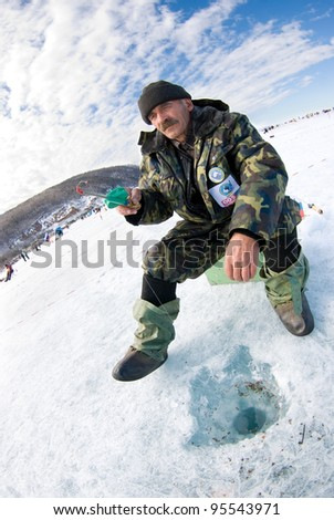 UST-BARGUZIN, RUSSIA - APRIL 11: An unidentified fisher sits with a rod at an ice hole during the 5th Annual Baikal Fishing, April 11, 2009 in Ust-Barguzin, Buryatia, Russia. - stock photo