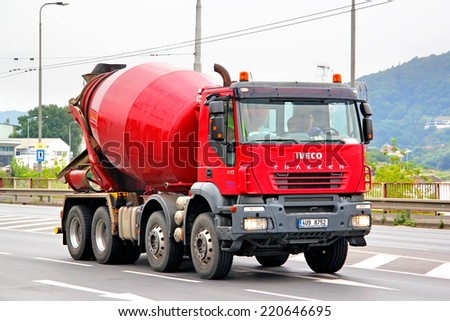USTI NAD LABEM, CZECH REPUBLIC - JULY 21, 2014: Red concrete mixer truck Iveco Trakker at the city street. - stock photo