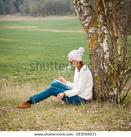 Usual pleasant hipster girl writes in a notebook and smokes. Dreamy girl on the nature