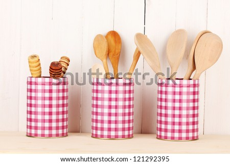 Utensils in metal containers isolated on light background