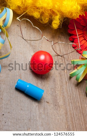 Utensils of a clowns costume laying on a wooden table