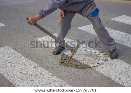 utilities worker moves the manhole cover to check the sewer line for clogs - stock photo