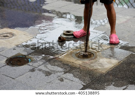 utilities workers moves the manhole cover to cleaning the sewer line for clogs - stock photo