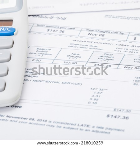 Utility bill and calculator - 1 to 1 ratio - stock photo