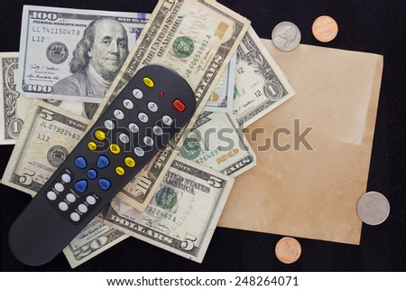 Utility bills - TV. TV remote switching channels with dollars and cents. - stock photo