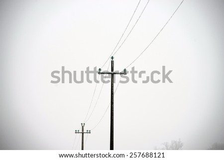 utility line poles in a frozen white countryside