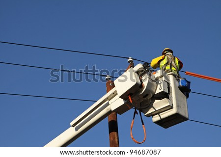 Utility Lineman Working on Cables Against Blue Sky - stock photo