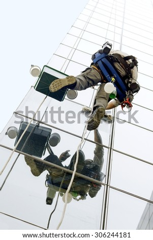 utility vertical climber worker hanging on ropes to cleaning the windows of a modern building - stock photo