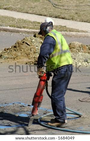Utility worker jackhammering street. - stock photo