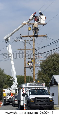 utility workers doing maintenance on power pole - stock photo