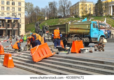 Utility workers in orange vests repair after riot and vandalism 2013-2014. Khreshatik - central street of Kiev.At April 8,2016 in Kiev, Ukraine - stock photo