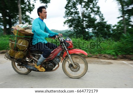 Uttaradit ,Thailand - June 27, 2013 :Farmer is riding a motorcycle  with baskets full of durians at Laplae Uttaradit , Thailand