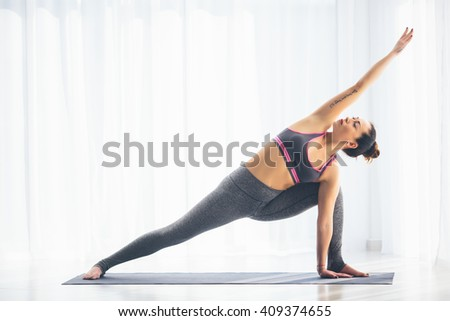 Utthita parsvakonasana. Beautiful yoga woman practice in a training hall background. Yoga concept.