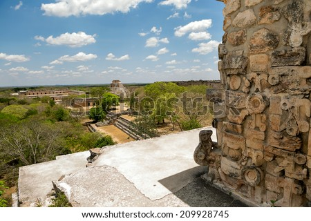Uxmal seen from top of a temple with architectural detail in the forefront - stock photo