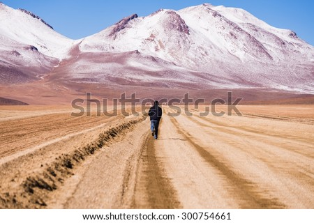 UYUNI, BOLIVIA Circa March 2015: a man running towards the mountaineous landscape