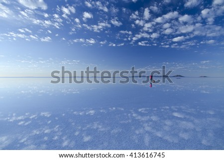 Uyuni morning, a man and clouds reflected surface of the water. A mirror in the sky.