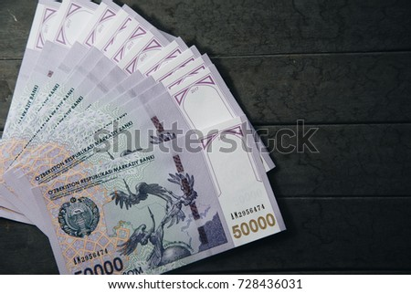 Uzbek banknotes on wooden background. Currency. Uzbek Money. Fifty Thousand Uzbek Sums 50000