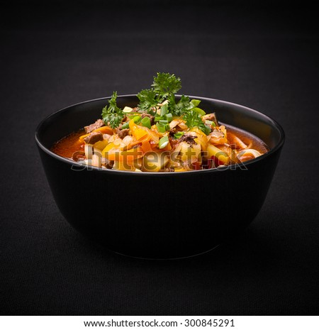 Uzbek noodle soup Lagman on black, close up - stock photo
