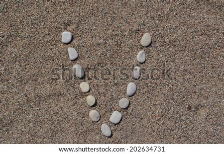 V letter made of stones on sand  - stock photo