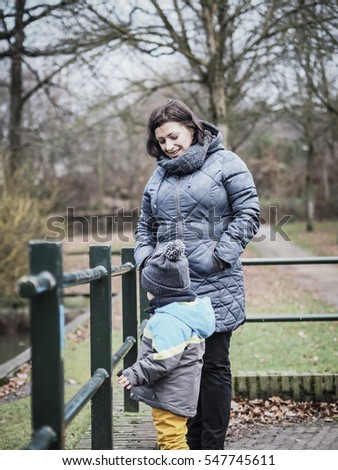 VAALS, THE NETHERLANDS - DECEMBER 25, 2016: Unidentified woman standing by a small young boy close to a barrier on a park
