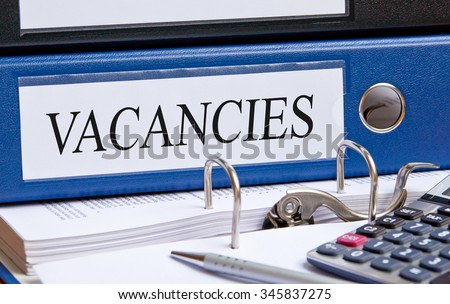 Vacancies - blue binder with text in the office - stock photo