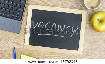 Vacancy written on a chalkboard at the office - stock photo