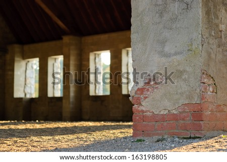 Vacant brick building interior with sunset light coming in through windows. - stock photo