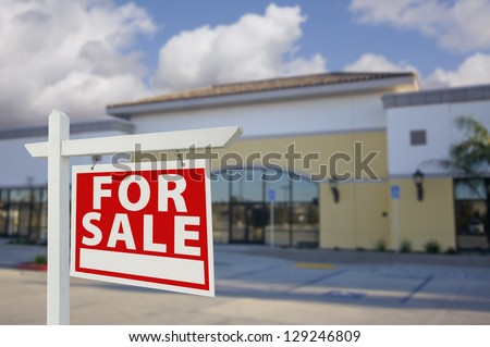 Vacant Retail Building with For Sale Real Estate Sign in Front. - stock photo