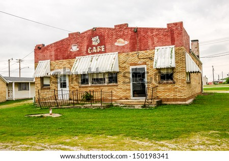 Vacant Route 66 Cafe in Illinois with faded awnings and a brick exterior in red, brown, and beige - stock photo