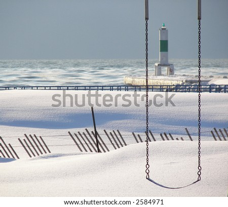 vacant swing on a winter beach with fence and Lake Michigan pier
