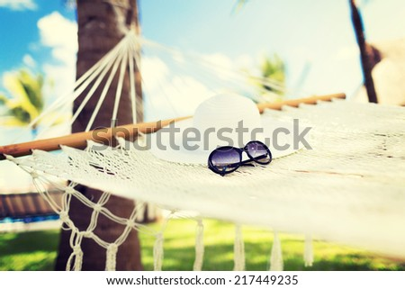 vacation and holiday concept - picture of hammock with white hat and sunglasses - stock photo