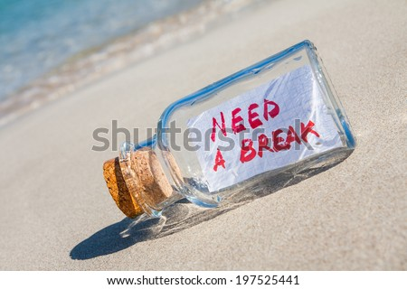 "Vacation and stress concept. Vintage bottle with text message ""need a break"" lying on a sandy beach  - stock photo"