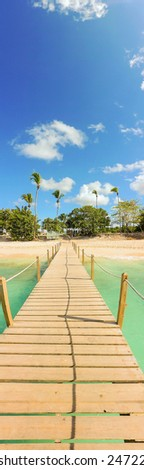 Vacation background: wooden jetty, beautiful exotic beach and palm trees - stock photo