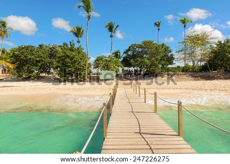 Vacation background: wooden jetty, exotic beach and palm trees - stock photo