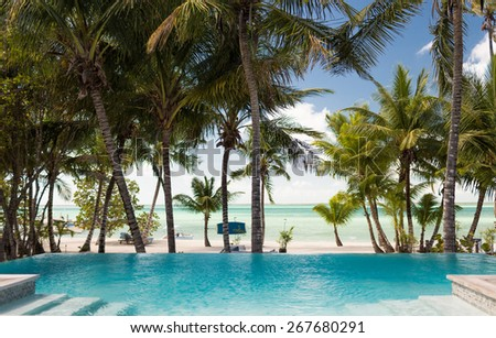 vacation, beach, summer and leisure concept - swimming pool on tropical beach - stock photo