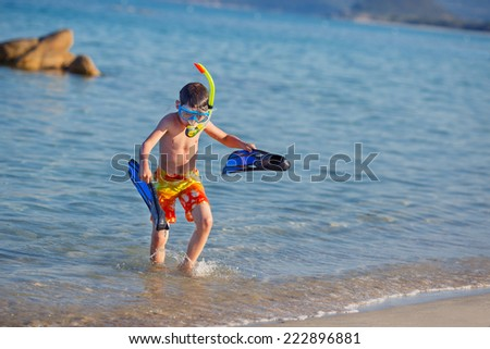 Vacation boy happy snorkeling running having fun in water splashing holding fins during summer holiday vacation - stock photo