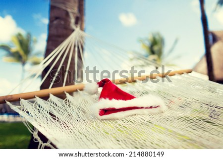 vacation, christmas and holiday concept - picture of hammock with santa helper hat - stock photo