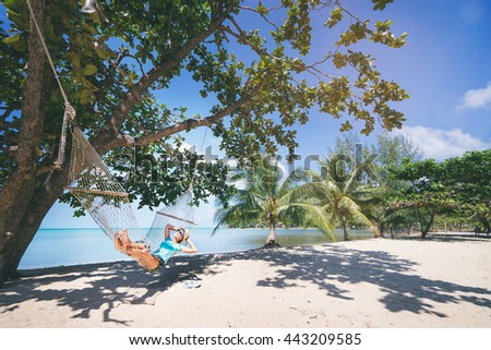Vacation concept. Enjoying the summer. Young pretty woman in hat and sunglasses laying in hammock on the beach. - stock photo