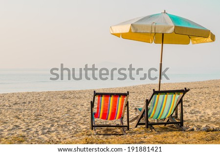 Vacation concept: Pair of beach loungers on the deserted coast  - stock photo