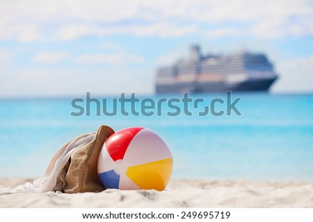 vacation concept, view of beach ball and beach bag at the sand with cruise ship in the background - stock photo