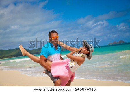 Vacation couple fun on beach, man giving piggyback ride. Man piggybacking woman girlfriend on  Waimanalo beach, Oahu, Hawaii, USA. Couple in love. Romantic holiday. - stock photo