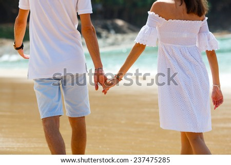 Vacation couple walking on beach together in love holding around each other - stock photo