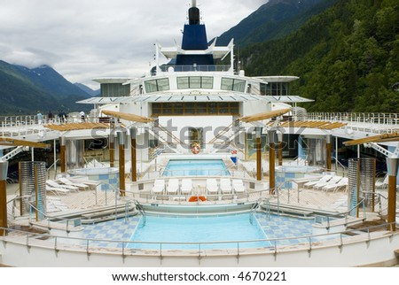 Vacation cruise ship main top deck swimming pool area in mountain harbor - stock photo