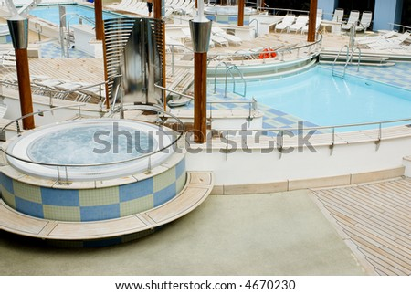 Vacation cruise ship main top deck swimming pool area with hot tub - stock photo