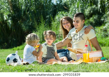 Vacation day of young family with picnic at countryside - stock photo