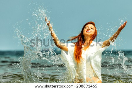 Vacation. Girl splashing water on the coast. Young woman having fun relaxing on the sea. Summertime. - stock photo