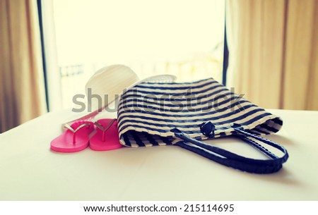 vacation, holiday and travel concept - close-up of beach bag, straw hat and flip-flop on hotel bed - stock photo