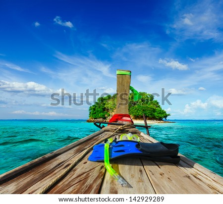 Vacation holidays adventure  concept background - tropical island and long-tail boat  with snorkeling set. Thailand - stock photo